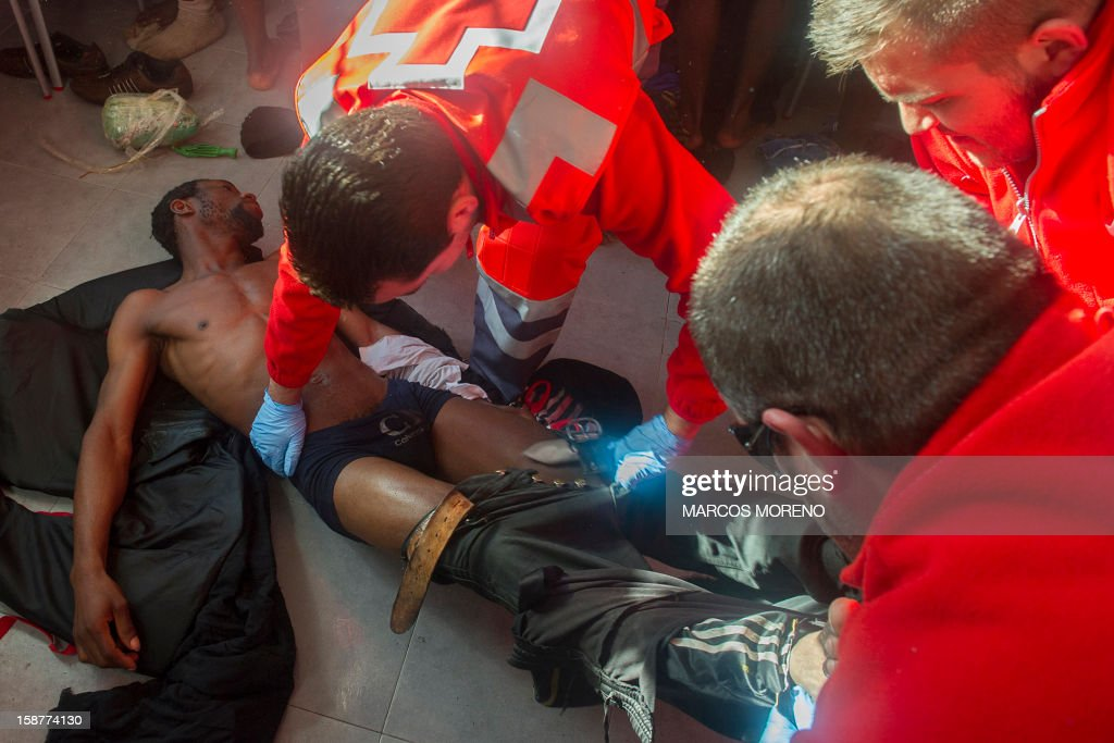 A would-be immigrant is treated by Spanish Red Cross emergency services in Tarifa, on December 28, 2012. Spanish rescuers intercepted today a boat carrying sub-Saharan would-be immigrants, 21 men, 7 women and 4 children accross the Strait of Gibraltar. Some of them suffered from hyporthermia.