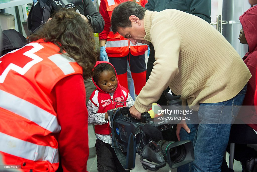 A would-be immigrant young child has a look at a TV camera at a Spanish Red Cross emergency services local in Tarifa, on December 28, 2012. Spanish rescuers intercepted today a boat carrying sub-Saharan would-be immigrants, 21 men, 7 women and 4 children accross the Strait of Gibraltar. Some of them suffered from hyporthermia.