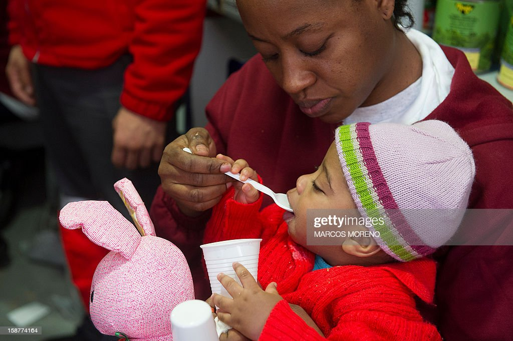 A would-be immigrant young child is feeded at a Spanish Red Cross emergency services local in Tarifa, on December 28, 2012. Spanish rescuers intercepted today a boat carrying sub-Saharan would-be immigrants, 21 men, 7 women and 4 children accross the Strait of Gibraltar. Some of them suffered from hyporthermia.