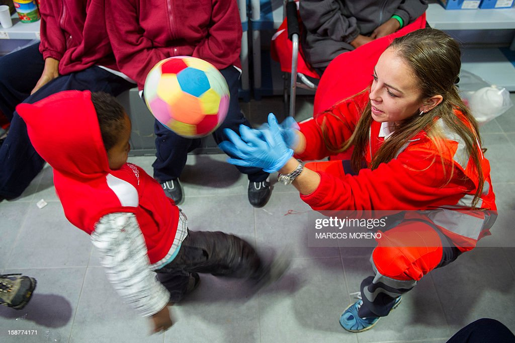 A would-be immigrant young child plays with a ball at a Spanish Red Cross emergency services local in Tarifa, on December 28, 2012. Spanish rescuers intercepted today a boat carrying sub-Saharan would-be immigrants, 21 men, 7 women and 4 children accross the Strait of Gibraltar. Some of them suffered from hyporthermia.