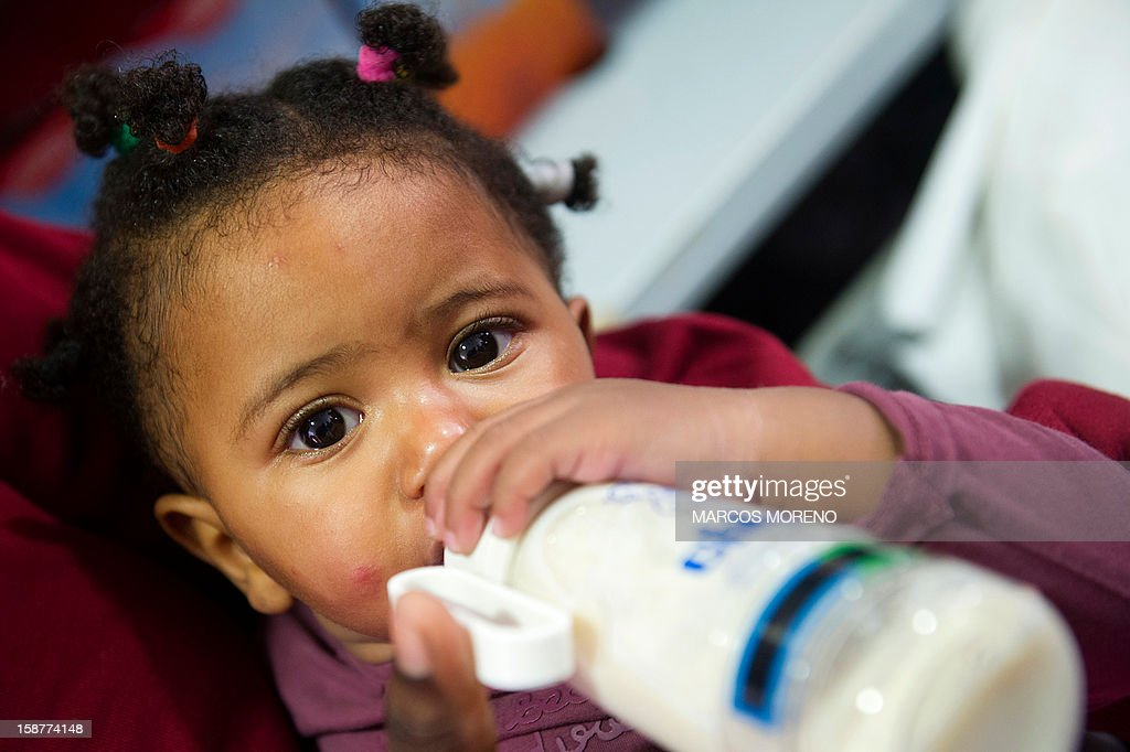 A would-be immigrant young girl drinks milk at a Spanish Red Cross emergency services local in Tarifa, on December 28, 2012. Spanish rescuers intercepted today a boat carrying sub-Saharan would-be immigrants, 21 men, 7 women and 4 children accross the Strait of Gibraltar. Some of them suffered from hyporthermia. AFP PHOTO/ MARCOS MORENO