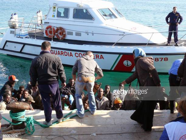 Wouldbe immigrants arrive aboard an inflatable raft escorted by an Italian Carabinieri patrol boat at a port on April16 2009 on the Italian island of...