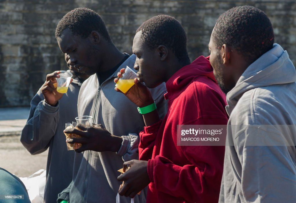 Would-be immigrants drink and eat after leaving the boat of the Spanish emergency services which rescued them off the Spanish coast and led to Tarifa, on May 4, 2013. Five boats carrying 66 sub-Saharan would-be immigrants were rescued, 4 by Morrocan emergency services and one by Spanish emergency services as they were crossing the Strait of Gibraltar. AFP PHOTO/ MARCOS MORENO