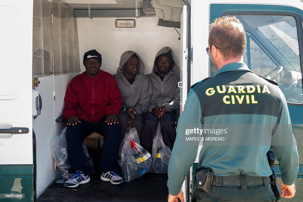 Would-be immigrants, kept under surveillance of Guardia Civil policeman, wait in a van after leaving the boat of the Spanish emergency services which rescued them off the Spanish coast and led them to Tarifa, on May 4, 2013. Five boats carrying 66 sub-Saharan would-be immigrants were rescued, 4 by Morrocan emergency services and one by Spanish emergency services as they were crossing the Strait of Gibraltar.