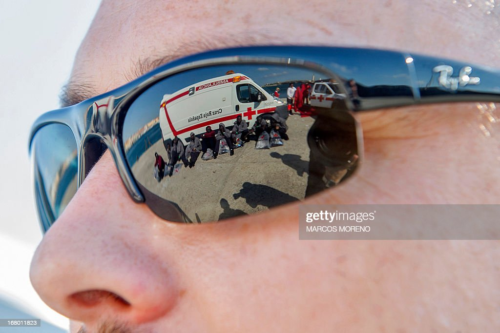 Would-be immigrants, reflected in the sunglasses of a Guardia Civil policeman, rest after leaving the boat of the Spanish emergency services which rescued them off the Spanish coast and led them to Tarifa, on May 4, 2013. Five boats carrying 66 sub-Saharan would-be immigrants were rescued, 4 by Morrocan emergency services and one by Spanish emergency services as they were crossing the Strait of Gibraltar.