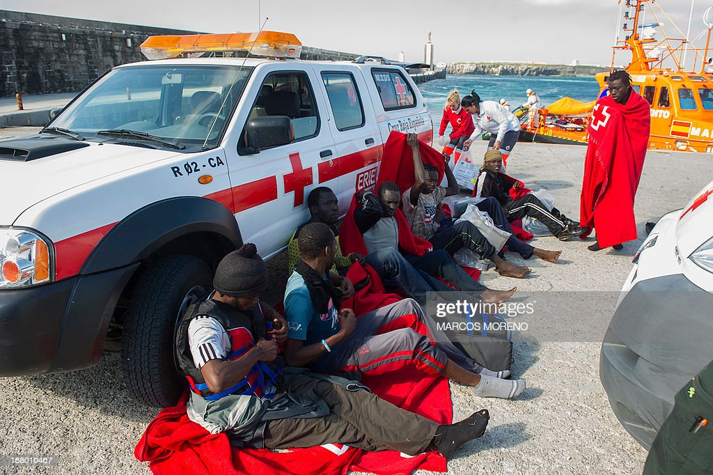 Would-be immigrants rest after leaving the boat of the Spanish emergency services which rescued them off the Spanish coast and led to Tarifa, on May 4, 2013. Five boats carrying 66 sub-Saharan would-be immigrants were rescued, 4 by Morrocan emergency services and one by Spanish emergency services as they were crossing the Strait of Gibraltar.
