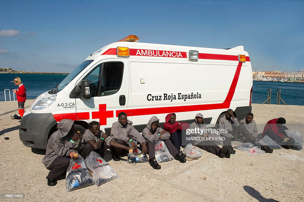 Would-be immigrants rest after leaving the boat of the Spanish emergency services which rescued them off the Spanish coast and led them to Tarifa, on May 4, 2013. Five boats carrying 66 sub-Saharan would-be immigrants were rescued, 4 by Morrocan emergency services and one by Spanish emergency services as they were crossing the Strait of Gibraltar.