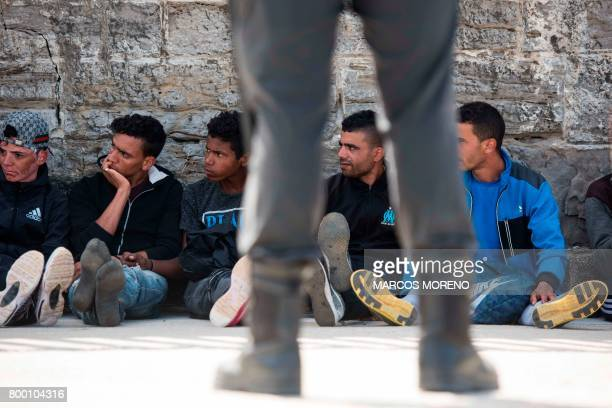 TOPSHOT Wouldbe immigrants sit and rest in the port of Tarifa following their rescue by salvage vessels off the Strait of Gibraltar coast on June 23...