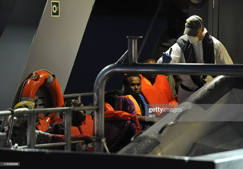 Would-be immigrants sit on a Maltese patrol vessel at Hay Wharf in Valletta, after being rescued on July 10, 2013. The Maltese military rescued a boatload of 68 undocumented migrants, a day after the European Commission warned Maltese Prime Minister Joseph Muscat against sending possible asylum-seekers back to Libya. AFP PHOTO / MATTHEW MIRABELLI