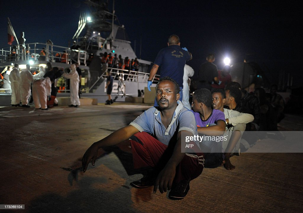 Would-be immigrants wait to bard a bus after disembarking from a Maltese patrol vessel at Hay Wharf in Valletta, after being rescued on July 10, 2013. The Maltese military rescued a boatload of 68 undocumented migrants, a day after the European Commission warned Maltese Prime Minister Joseph Muscat against sending possible asylum-seekers back to Libya. AFP PHOTO / MATTHEW MIRABELLI