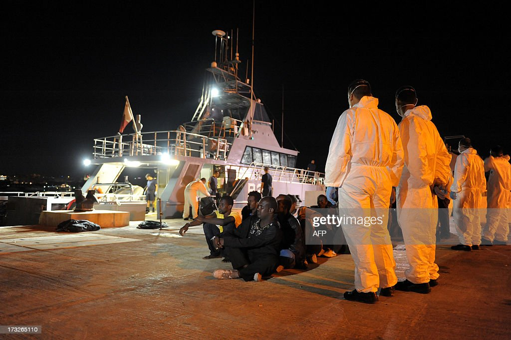 Would-be immigrants wait to bard a bus after disembarking from a Maltese patrol vessel at Hay Wharf in Valletta, after being rescued on July 10, 2013. The Maltese military rescued a boatload of 68 undocumented migrants, a day after the European Commission warned Maltese Prime Minister Joseph Muscat against sending possible asylum-seekers back to Libya.
