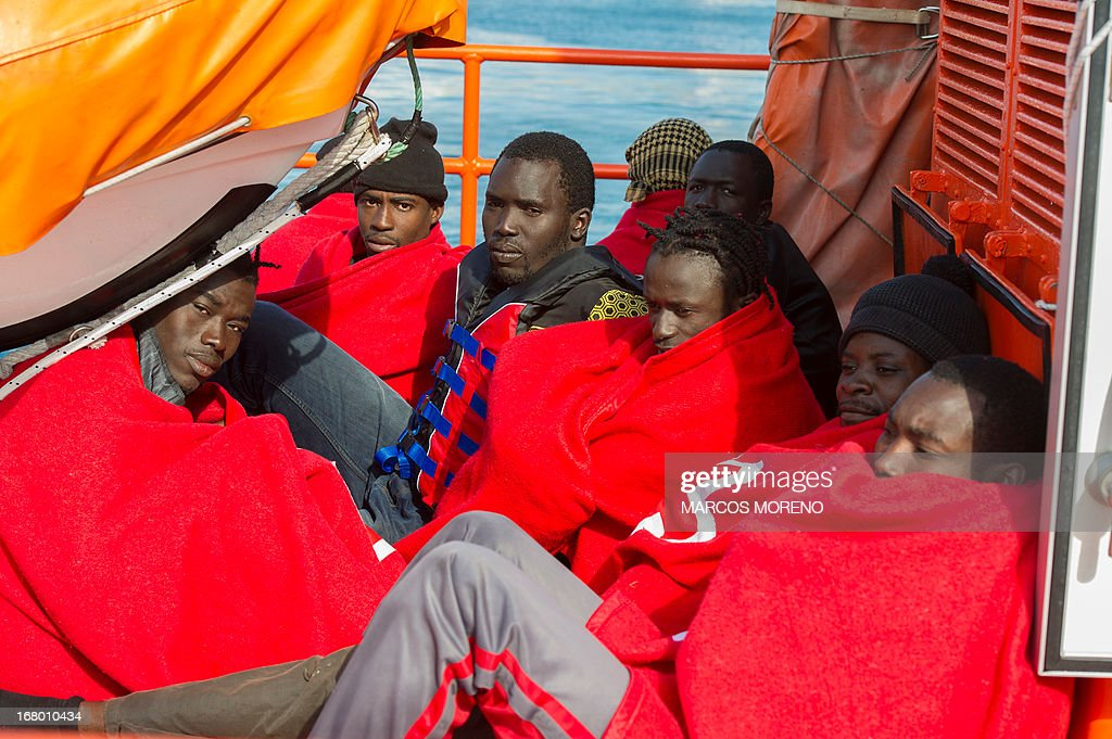 Would-be immigrants with blankets sits in a boat of the Spanish emergency services after being rescued off the Spanish coast and led to Tarifa, on May 4, 2013. Five boats carrying 66 sub-Saharan would-be immigrants were rescued, 4 by Morrocan emergency services and one by Spanish emergency services as they were crossing the Strait of Gibraltar.