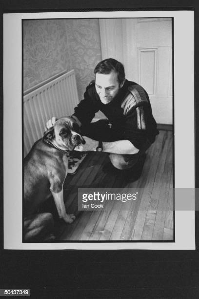 Wouldbe screenwriter Douglas Gresham son of Amer poet Joy Gresham executor of his stepdad CS Lewis's estate petting his boxer dog at home