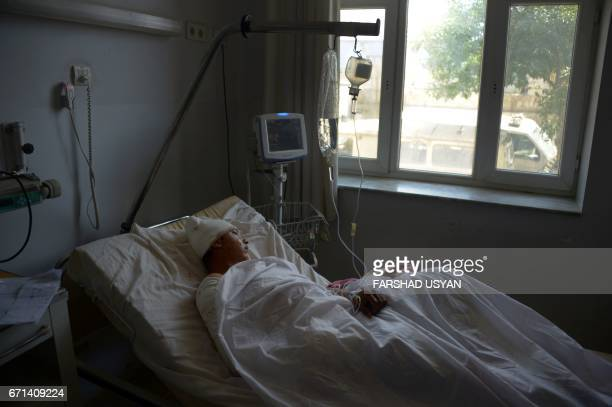 A wounded Afghan National Army soldier lies on a bed in the ward of a hospital in MazariSharif on April 22 as he receives treatment following an...