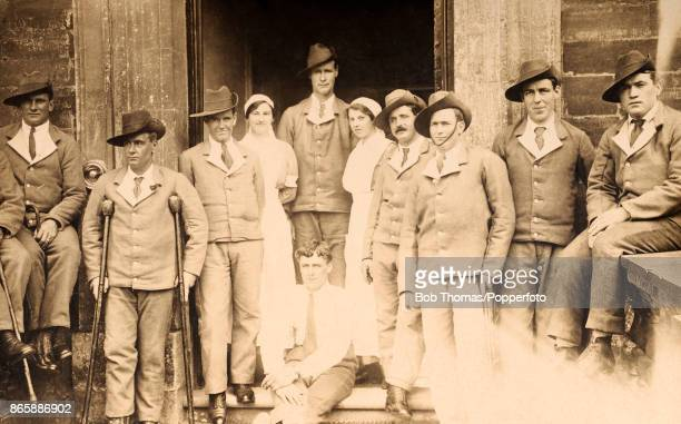 Wounded Australian soldiers wearing their 'hospital blues' and posing with their nurses at a military hospital near Leicester England circa 1917