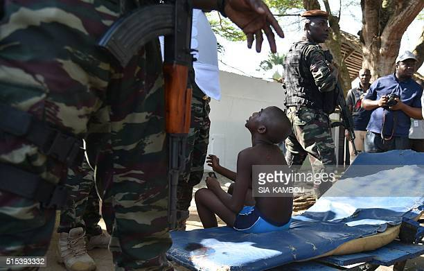 A wounded child is surrouned by Ivorian security forces after heavily armed gunmen opened fire on March 13 2016 at a hotel in the Ivory Coast beach...