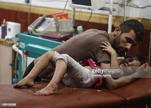 A wounded child is treated in hospital after Syrian regime attack on residential areas in Douma Eastern Ghouta Damascus on September 13 2015