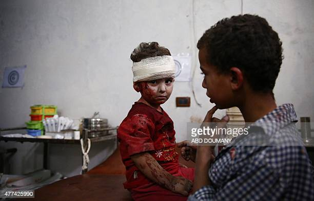 A wounded child looks on after receiving treatment at a makeshift medical centre in Douma on the northeastern outskirts of the Syrian capital...