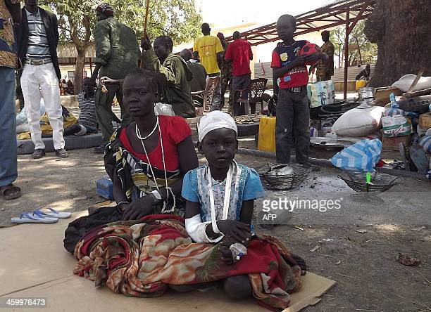 A wounded child sits next to a relative after receiving treatment at the Malakal Hospital in the Upper Nile State of South Sudan on December 31 2013...