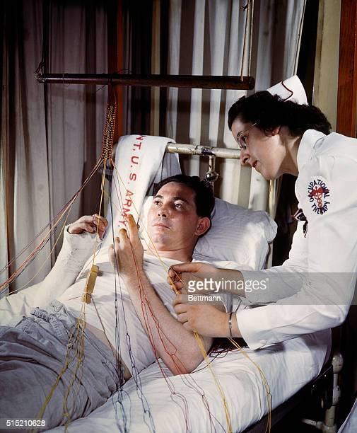 3/12/1944 Wounded convalescing at Walter Reed Hospital A nurse is by his side as he weaves a craft in bed