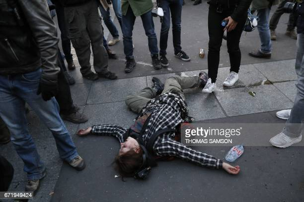 TOPSHOT A wounded demonstrator lies on the ground during a demonstration called by antifascists in Paris on April 23 2017 following the announcement...