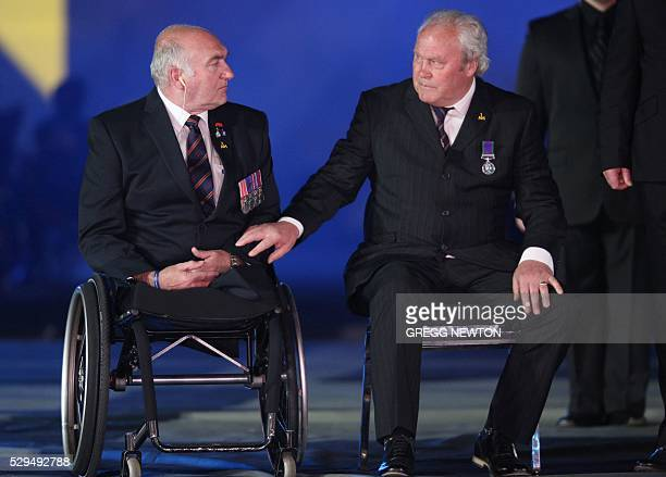 A wounded exserviceman reaches out to another before their choir performance of 'Flesh and Blood' featuring Laura Wright during opening ceremonies...