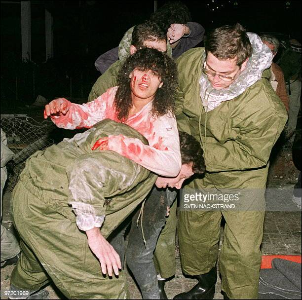 A wounded Israeli woman bleeding from a head is evacuated by rescuers after an Iraqi Sovietmade Scud missile exploded downtown Tel Aviv 22 January...