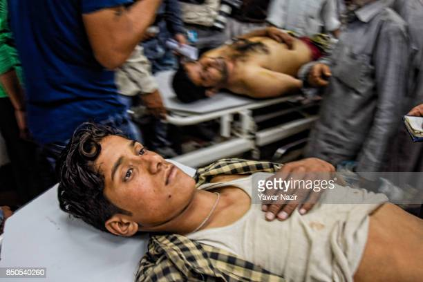 Wounded Kashmiri civilians wait for treatment inside a hospital after a grenade attack in a busy market which killed three civilians on September 21...