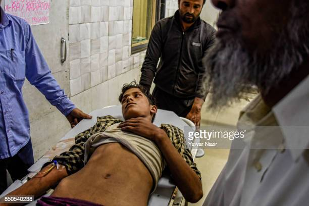 A wounded Kashmiri Muslim boy waits for treatment inside a hospital after a grenade attack in a busy market which killed three civilians on September...