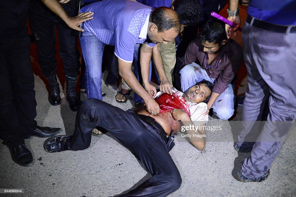 A wounded man is helped near a restaurant that has been attacked by unidentified gunmen in the early hours of July 2, 206 in Dhaka, Bangladesh. Gunmen have taken at least 20 foreigners hostage at a restaurant in the diplomatic area of Dhaka, the capital of Bangladesh.