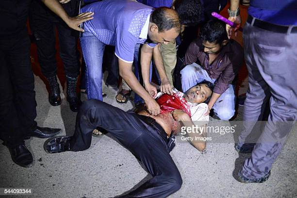 A wounded man is helped near a restaurant that has been attacked by unidentified gunmen on July 1 2016 in Dhaka Bangladesh Gunmen have taken at least...