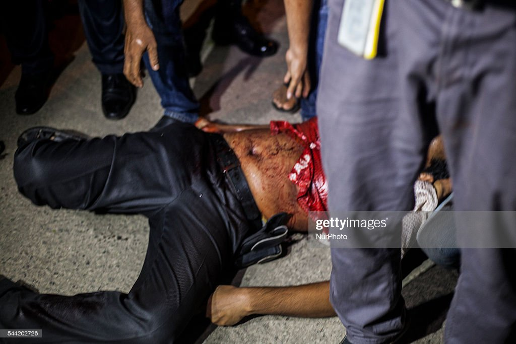 A wounded man is helped near a restaurant that has been attacked by unidentified gunmen in the early hours of July 2, 206 in Dhaka, Bangladesh. Gunmen have taken at least 20 foreigners hostage at a restaurant in the diplomatic area of Dhaka, the capital of Bangladesh. So-called Islamic State have claimed reponsibility for the attack, which has reportedly left at least 2 police officers dead and many more people injured.