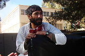 A wounded man is seen after suspected Taliban suicide bombers and gunmen attacked a bank in the Helmand province of Afghanistan on December 17 2014 A...