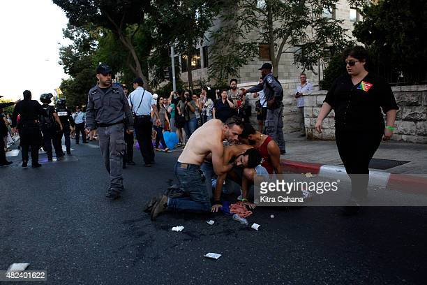 A wounded man is treated after getting stabbed while marching in the gay pride parade on July 30 2015 in downtown Jerusalem Israel At least six...