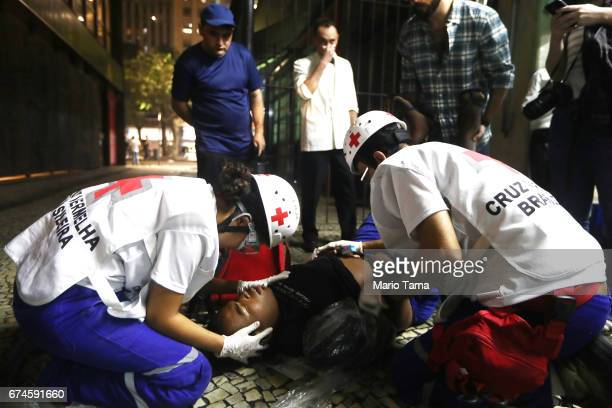 A wounded man is treated by Red Cross workers during protests during a nationwide general strike on April 28 2017 in Rio de Janeiro Brazil The...