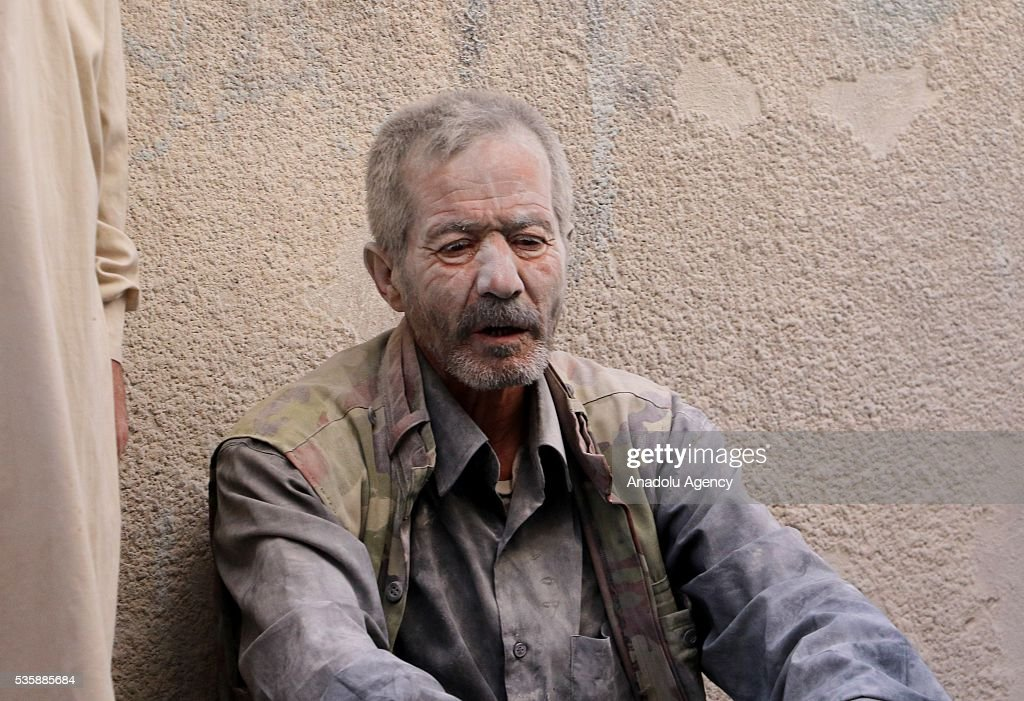 A wounded man sits near a wall after Assad forces hit residential areas with 'naval mines', thrown from helicopters in Kallese District of Aleppo, Syria on May 30, 2016.
