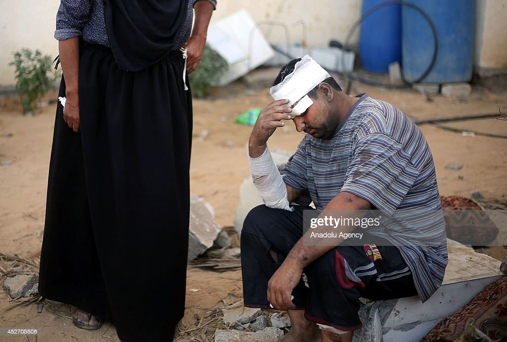 A wounded member of En-Neccar family is seen as search and rescue team and Palestinians search at the wreckage of a building, belongs to Palestinian En-Neccar family, in Khan Yunis, Gaza on July 26, 2014. Israeli assault, hit house of Palestinian En-Neccar family in Khan Yunis, killed 16 members of family and wounded 20 others in Gaza. The new fatalities raise Gaza's death toll from Israel's war to 900 since the beginning of this war on July 7.