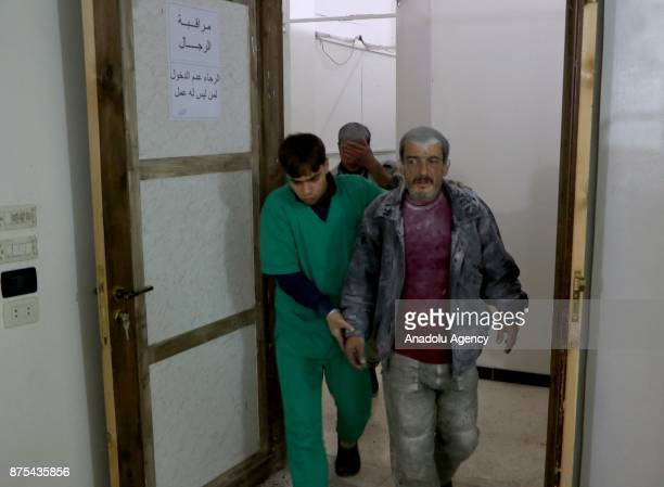 Wounded men arrive to receive medical treatment after Assad regime's war crafts carry out intensifying airstrikes over residential areas of Arbin...