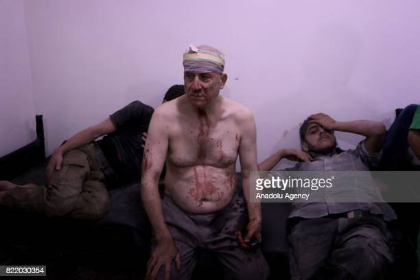 Wounded men wait to receive treatment at a sahra hospital after Assad Regime's forces carried out airstrike over the deconflict zone Arbin town in...
