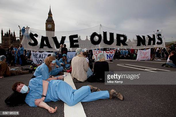 Wounded nurse lies in front of a banner saying Save our NHS UK Uncut shut down Westminster Bridge in a protest over NHS bill Thousands of protesters...