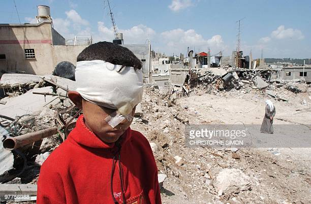 A wounded Palestinian boy stands on his destroyed house in the Jenin refugee camp 18 April 2002 The camp saw some of the fiercest fighting in...