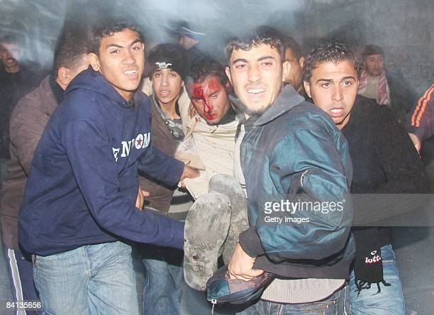 A wounded Palestinian is carried by men after an Israeli missile struck a neighbouring home of Hamas military leader on December 29 2008 in Beit...
