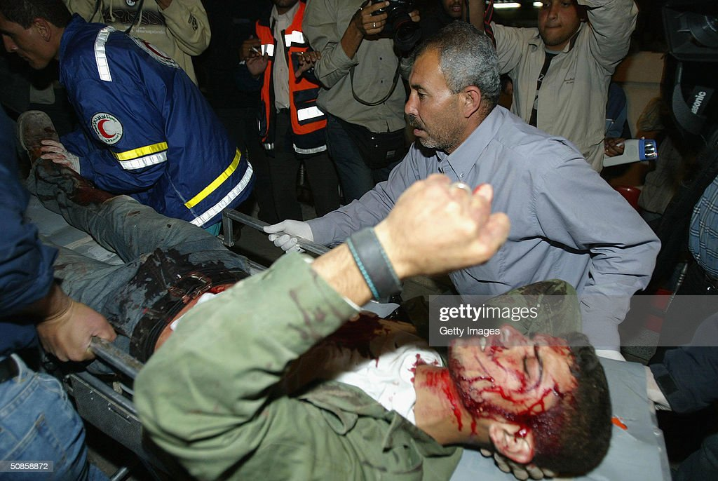 A wounded Palestinian is carried to hospital at the Rafah refugee camp, May 20, 2004, southern Gaza Strip. According to witnesses, Israeli helicopters fired missiles at the camp. Israel defied international fury at the killing of nearly 40 Palestinians in the Rafah refugee camp, a militant stronghold, to expand its bloodiest Gaza Strip raid in years on Thursday.