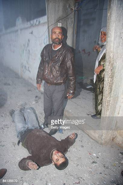 A wounded Palestinian man lies on the floor after an Israeli missile struck the neighbouring home of a Hamas military leader on December 29 2008 in...