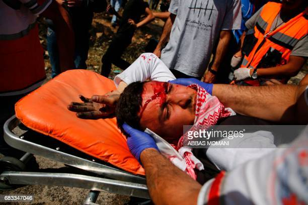 A wounded Palestinian protester receives first aid after being injured during clashes with Israeli security forces following a protest marking the...
