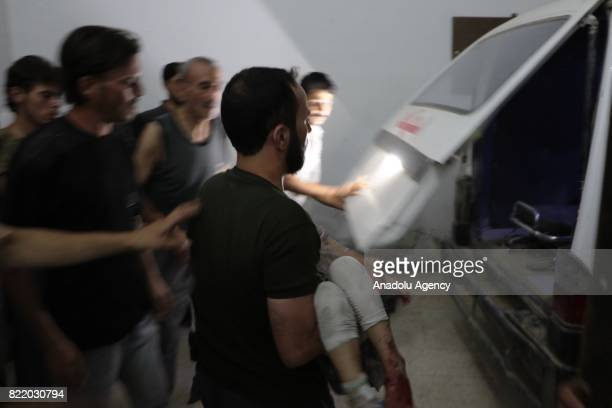 Wounded people are carried to a vehicle after Assad Regime's forces carried out airstrike over the deconflict zone Arbin town in the Eastern Ghouta...