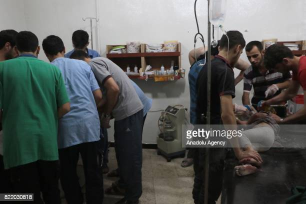 Wounded people receive treatment at a sahra hospital after Assad Regime's forces carried out airstrike over the deconflict zone Arbin town in the...