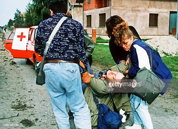 A wounded Serbian civilian is taken by volunteers to a car to be driven to an hospital 26 August 1991 in Borovo Selo AFP PHOTO
