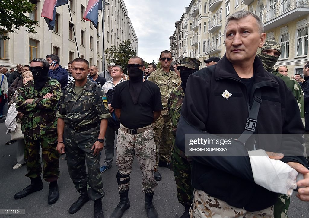 Wounded serviceman of a Ukrainian volunteer battalion of Donbass together with others rally in front of Ukrainian President Petro Poroshenko's office in Kiev on August 27, 2014. Protesters demand the President to help the volunteer battalions of Donbass, Mirotvorets, Kherson and Dnipro-1 surrounded by pro-Russian militants for the fifth day in the small city of Izvaryne, suburb of the eastern Ukrainian city of Donetsk.