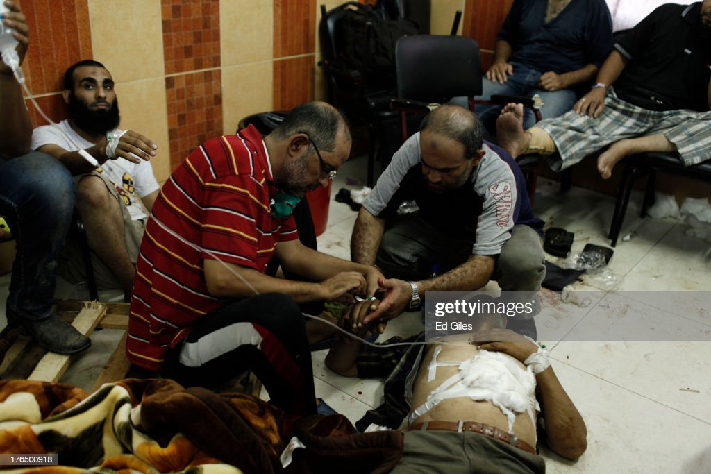 A wounded supporter of deposed Egyptian President Mohammed Morsi is treated by medical staff on the floor of the Rabaa al-Adaweya Medical Centre in the Nasr City district on August 14, 2013 in Cairo, Egypt. An unknown number of pro-Morsi protesters were killed in Egypt's capital today as Egyptian Security Forces undertook a planned operation to clear Morsi supporters from two sit-in demonstrations in Cairo where they have camped for over one month. Egyptian Police and Army forces entered protest sites in the Nasr City and Giza districts at dawn using tear gas, live fire and bulldozers to disperse protesters and destroy the camps. A state of emergency has been declared in Egypt to begin this afternoon and will reportedly last for one month.